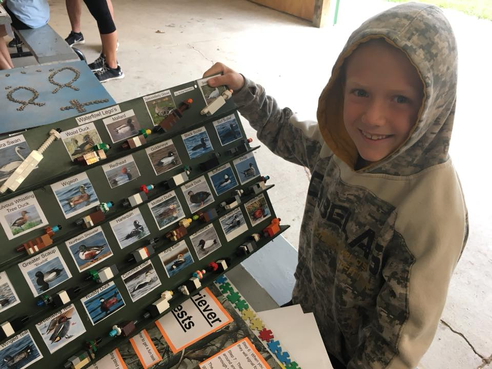 4-H member showing his waterfowl identification project with legos